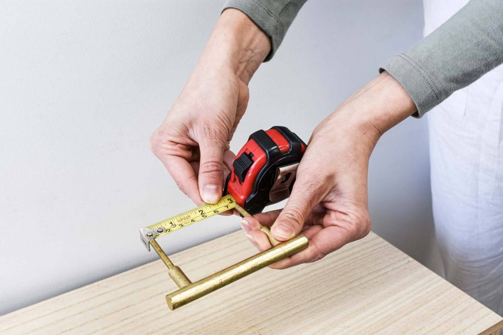 6 . MEASURE HANDLE HOLES 1024x683 - How to Install Cabinet Handles with New Screw Holes